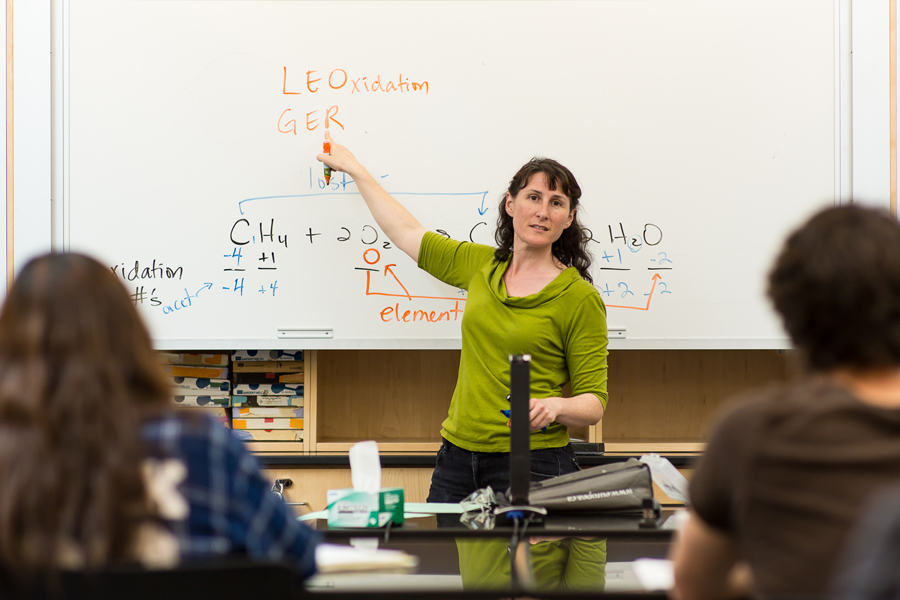 Dr. Heather Price lectures at whiteboard in front of a chemistry students.